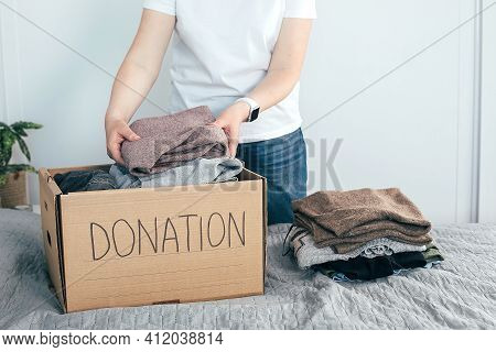 Donation Concept. Young Woman In White T-shirt With Donation Box At Home. Woman Donates Clothes. Lif