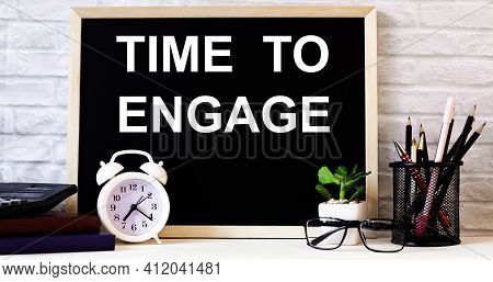 The Words Time To Engage Is Written On The Chalkboard Next To The White Alarm Clock, Glasses, Potted
