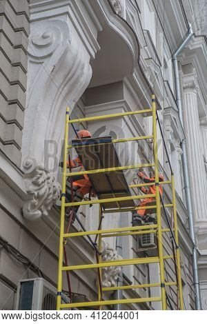 Workers Restore The Facade Of An Old Building