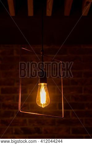 Metal Chandelier With Retro Orange Incandescent Lamp In A Restaurant Against Brick Wall Background