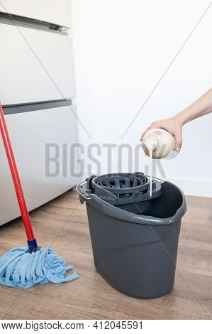 Close Up Of Woman Hand Putting Floor Cleaners In The Mop Bucket.concept Of Cleanliness At Home