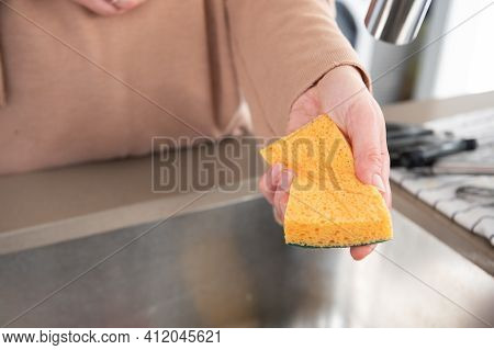 Close Up Of Woman's Hands Holding A Cleaning Sponge In The Kitchen.home Clean Concept