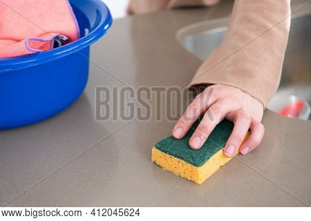 Close Up Of Woman's Hands Cleaning Kitchen Counter Top With A Scouring Pad. Nearby They Have Bucket