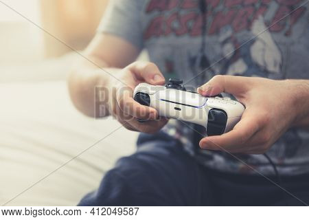 Selby, Uk - March 11, 2021. Close Up Of A Male Gamer Playing Online Video Games And Using A Ps5 Wire