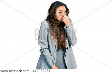 Young hispanic girl wearing business clothes and glasses smelling something stinky and disgusting, intolerable smell, holding breath with fingers on nose. bad smell