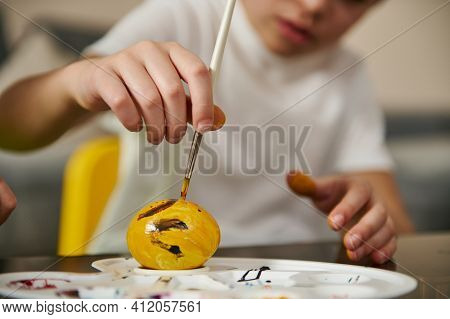 A Yellow Easter Egg On A Palette And A Boy's Hand Holding A Paintbrush And Decorating It For Easter.