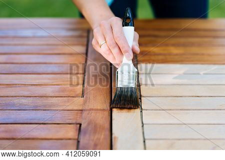 Renovation Of A Garden Table With A Paintbrush And Oil By A Young Girl On The Terrace