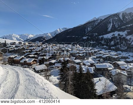 Snow Covered Mountain Village Of Munster Inf Valais, The First Rays Of Sunshine Are Shining Over The