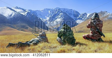 Men In Camouflage With Binoculars And Weapons Inspect The Foothills. Three Hunters Sitting And Lying