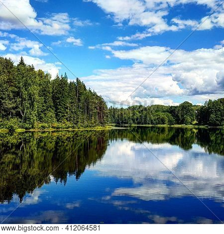 Summer Landscape With A Lake Surrounded By Forest In Which A Blue Sky With White Cumulus Clouds Is R