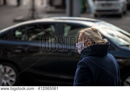 Belgrade, Serbia - March 6, 2021:  Old Woman Walking And Looking At A Street Traffic On A Boulevard