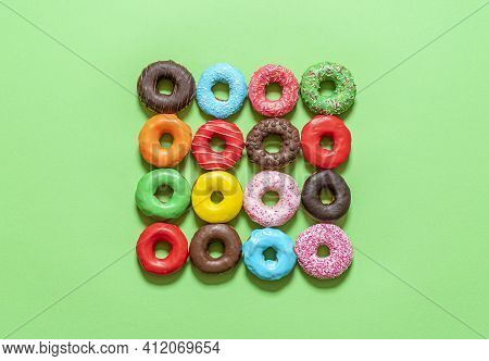 Multicolored Icing Doughnuts Arranged Symmetrically In A Square On A Green Background. Homemade Choc