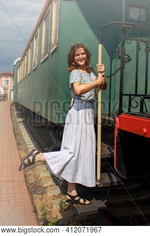 A Young Woman Sits In The Departing Retro Train Vintage Cars In The Style Of The Early 20th Century