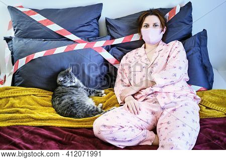 A Young Woman Lies In Bed With A Cat Quarantined From Coronavirus. Woman In A Homemade Medical Mask