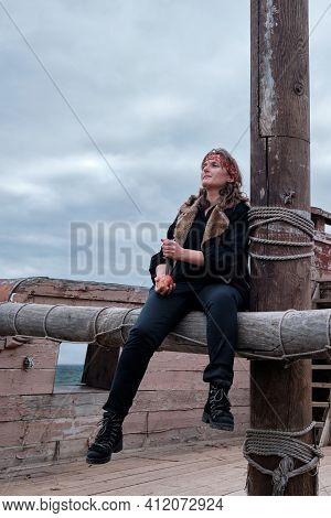 A Pirate Woman In A Bandanna Sits With A Dirk In Her Hand On A Wooden Deck Near The Mast Of A Sailin