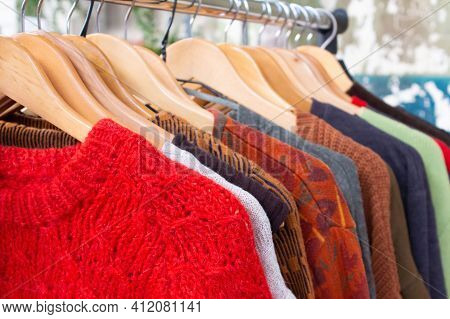 Second Hand Clothes On Hangers For Donation And Reselling. Garage Sale Or Economiv Shopping Concept.