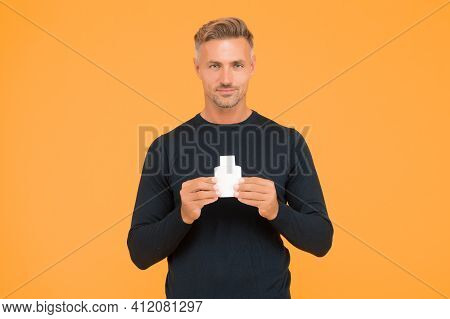 Apply Fragrance On Your Skin. Handsome Man Hold Perfume Bottle Yellow Background. Mens Grooming. Ski
