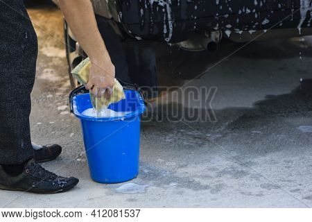 Home Car Washing Process. Mix Shampoo With Water. A Bucket With A Sponge. Washing Sponge, In Hands,