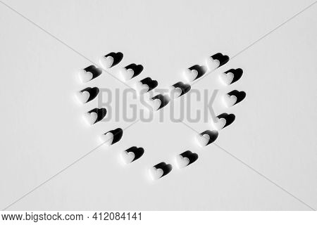 White Tablets Laid Out In Shape Of Heart. Hard Shadows. Concept Of Health, Pharmaceuticals And Medic