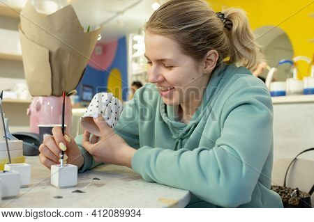 Smiling Young Woman In Casual Clothes Maks Ornament On Teecup In A Ceramic Workshop. Learning New Sk
