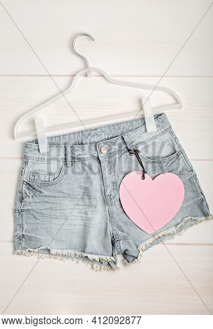 White Rack With Heart Tag And Jeans Shorts. Slow Fashion, Circular Economy, Eco Friendly Sustainable