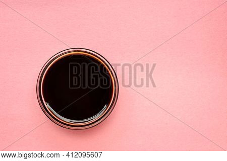 a small bowl of yacon syrup against pink paper with a copy space,  a powerful prebiotic sweetener derived from the yacon root
