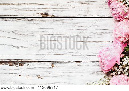Top View Of Pink Peonies And Baby's Breath Flowers Over A White Rustic Wood Table Background  With F