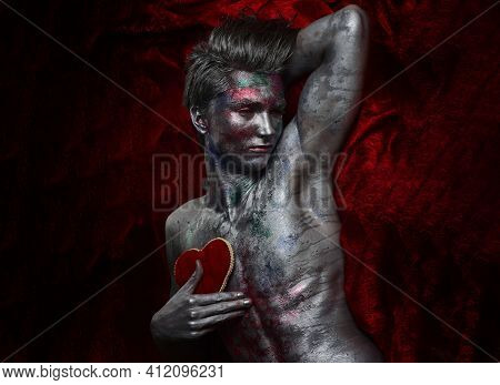 Art Man With Nude Torso Holds Red Soft Heart On Chest. Guy On Sad Face Covered With Shimmering Silve