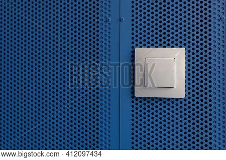 Electrical Switches. Plastic Electrical Switch On A Blue Metal Mesh Wall.background On The Topic Of