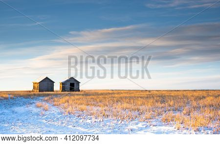 Two Old Vintage Farm Sheds Sit On A Winter Harvested Field On The Canadian Prairies In Rocky View Co
