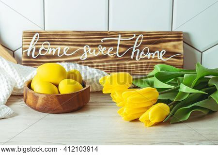 Home Sweet Home Handwritten Sign On Kitchen Countertop, Next To Wooden Bowl With Yellow Easter Eggs
