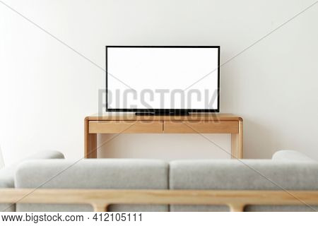 Blank white smart TV screen on a wooden table
