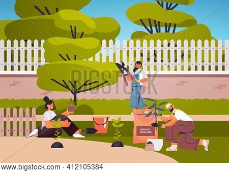 Gardeners Taking Care Of Plants People Working Together Planting Gardens Flowers In Backyard Gardeni