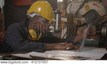 American Industrial Black Young Worker Man With Yellow Helmet And Ear Protection Typing Keyboard Of