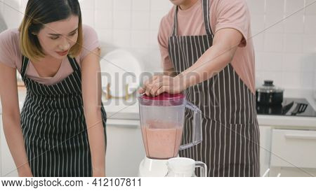 Happy Young Family Couple Husband And Wife Making Fresh Apple Smoothie In Kitchen Together. The Man