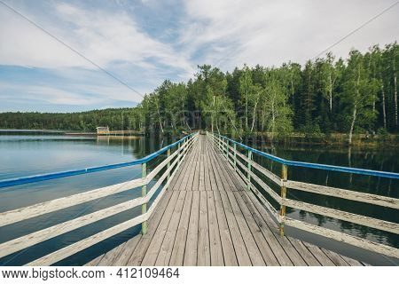 Fishing Bridge By The River. Docks For Boats On The Lake. Water And Transport