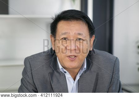Portrait Of Senior Asian Businessman Talking In Meeting Room With Online Meeting By Vedio Camera