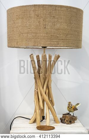 A Table Lamp Constructed Of Wooden Sticks And Hessian Shade Beside An Ornamental Bird