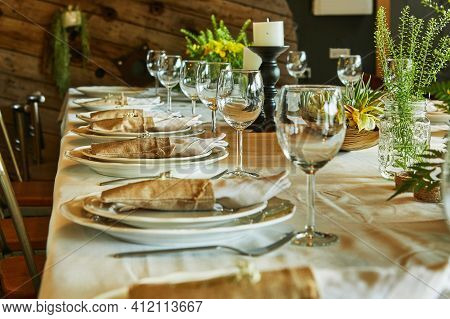 Laid Table With Cutlery And Crockery In The Sunset Sunlight.