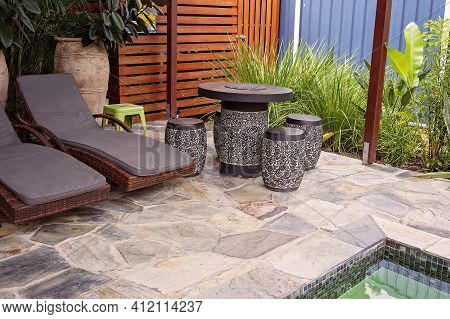Loungers With Ornate Carved Table And Stools In Landscaped Pool Surrounds