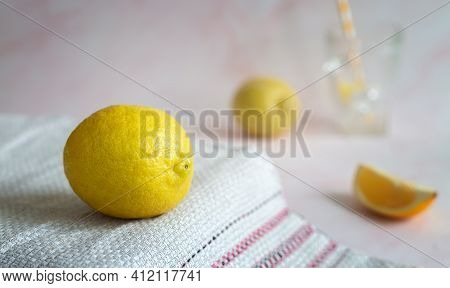 Lemon And A Slice Of Lemon On The Table On A Napkin. In The Background-glasses For Making A Lemon Dr