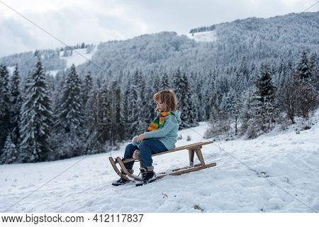 Funny Kid In Snow Ride On Sled, Sleigh. Winter Outdoors Games. Happy Christmas Family Vacation Conce