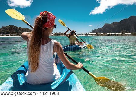 Two Young Girls Walks By Sea Kayaks Or Canoes At Lagoon With Turquoise Water. Phi-phi Don Island. Kr