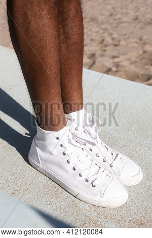 White sneakers closeup men's apparel summer fashion beach photoshoot