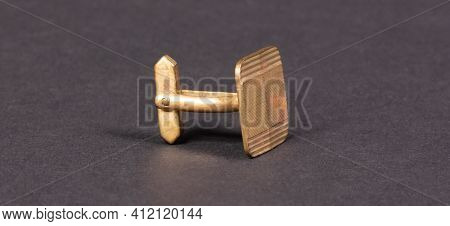 Old Gilded Cufflink, Isolated On Dark Background (with Shadow)
