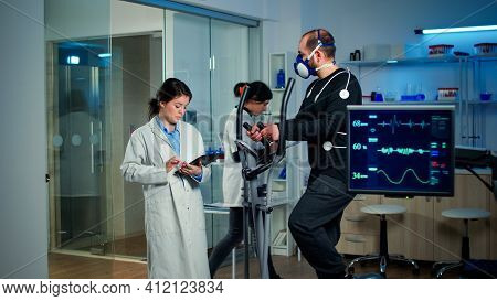 Sportsman With Mask Running On Cross Trainer In Sports Science Laboratory Measuring Vo2 Max, Heart R