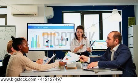 Team Leader Explain To Multiracial Workmates New Project Standing At Desk In Broadroom, Holding Clip