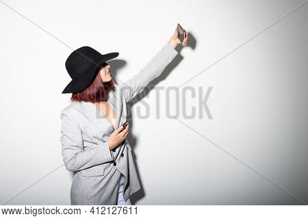 Young stylish woman using smartphone, indoor portrait over white. Fashion modern girl wearing grey jaket and black hat taking selfie photo with mobile phone