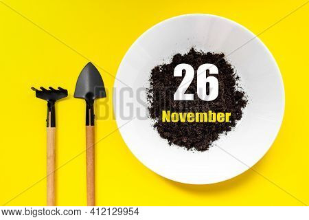 November 26th. Day 26 Of Month, Calendar Date. White Plate Of Soil With A Small Spatula And Rake On