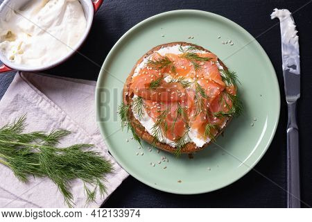 Half Bun Oiled With Fresh Cream, Decorated With Smoked Fish And Sprinkled With Fresh Dill And Sesame